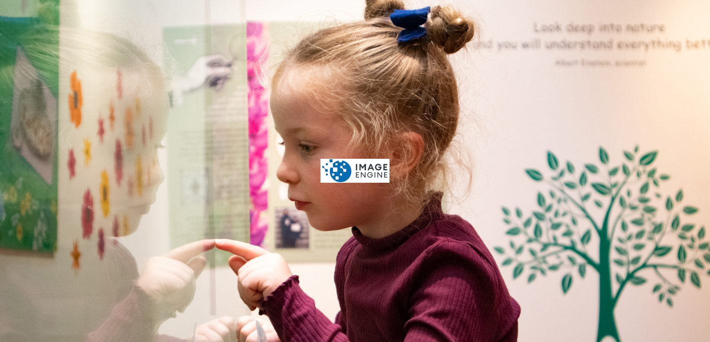Young girl looking at object in exhibition